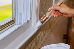 Closeup image of mans hand with paintbrush while painting window trim