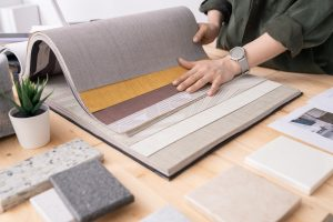 Hands of young designer of interior looking through samples of wallpapers