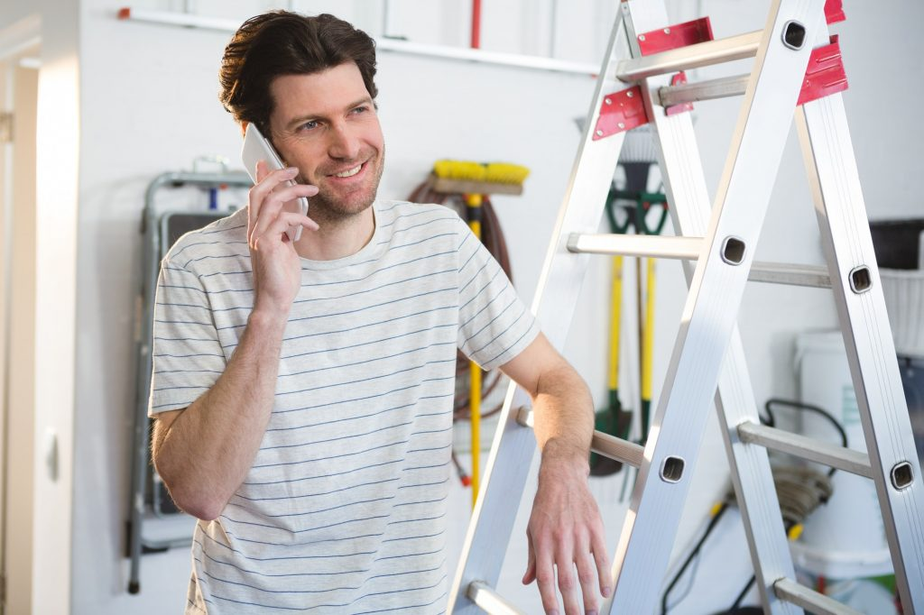 Male painter talking on mobile phone in workshop