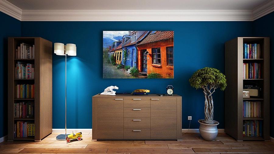 Byrå med målning ovanför och blå färg på väggen bakom